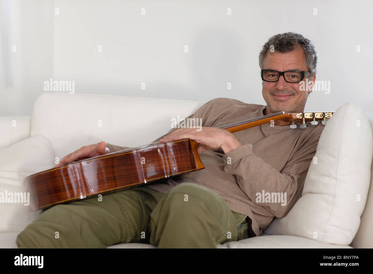 Man sitting with guitar - Stock Image