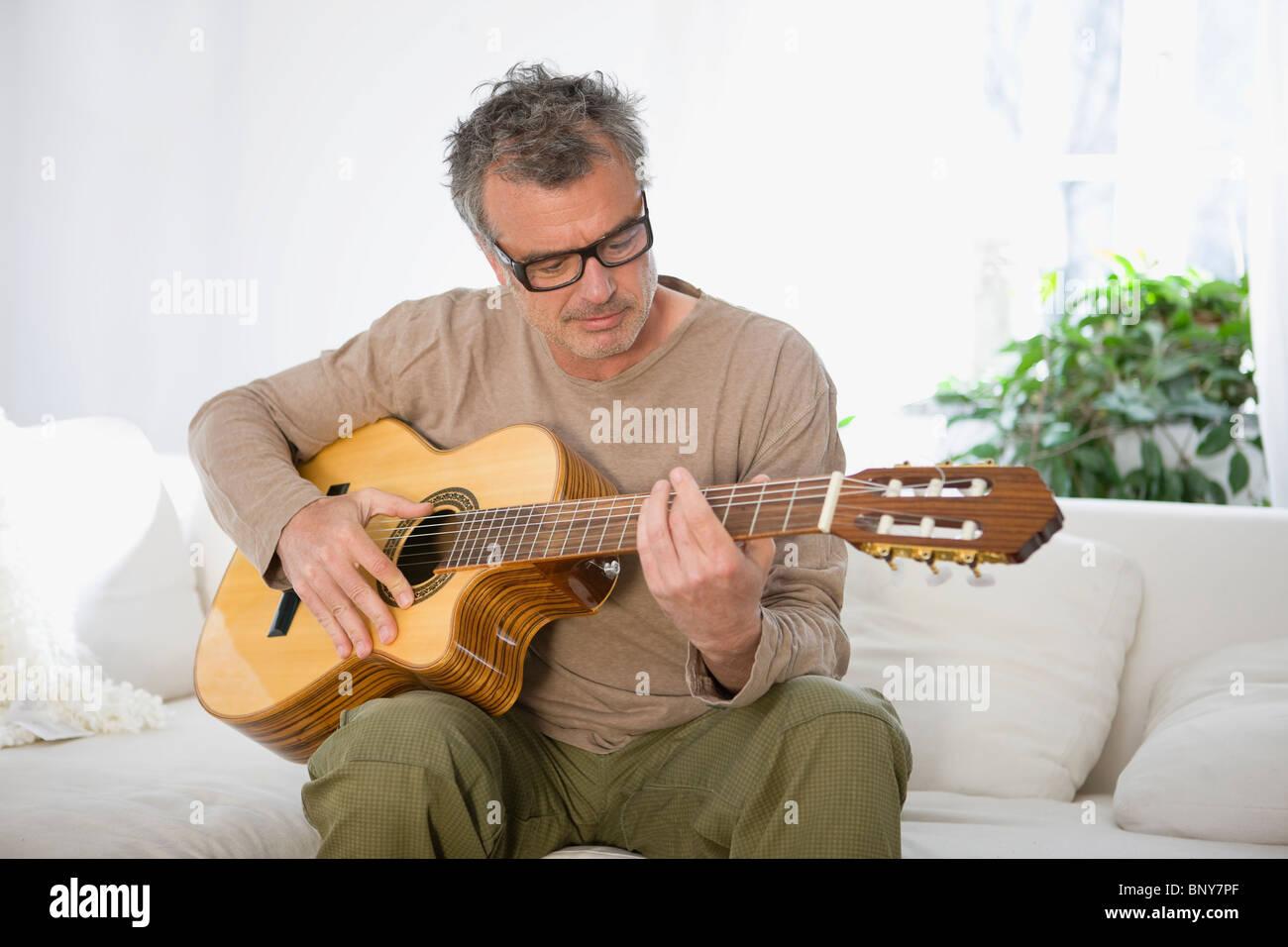 Man strumming guitar - Stock Image
