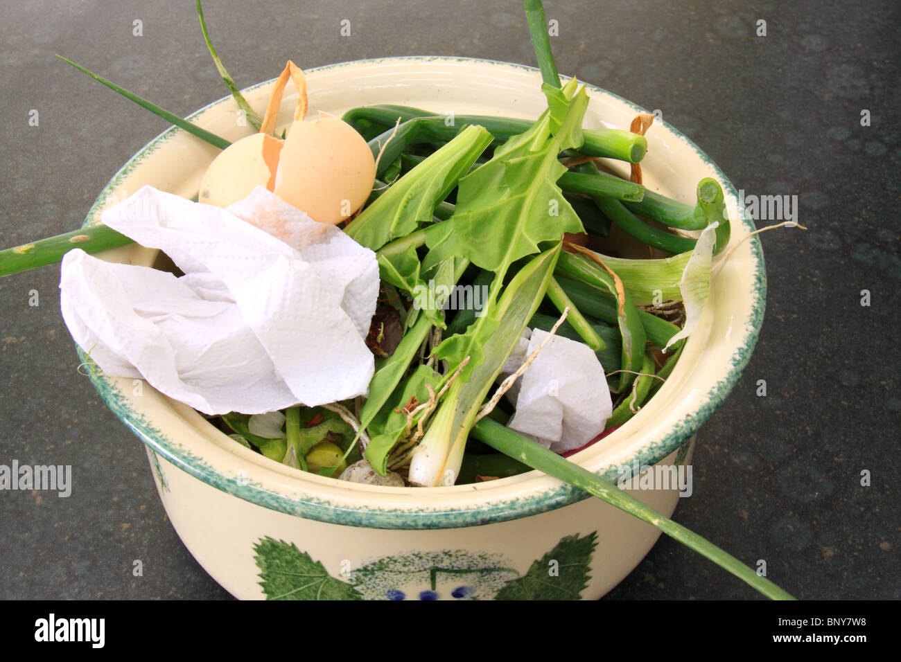 Ceramic casserole containing vegetable trimmings, egg shell and paper and destined for the compost heap. - Stock Image