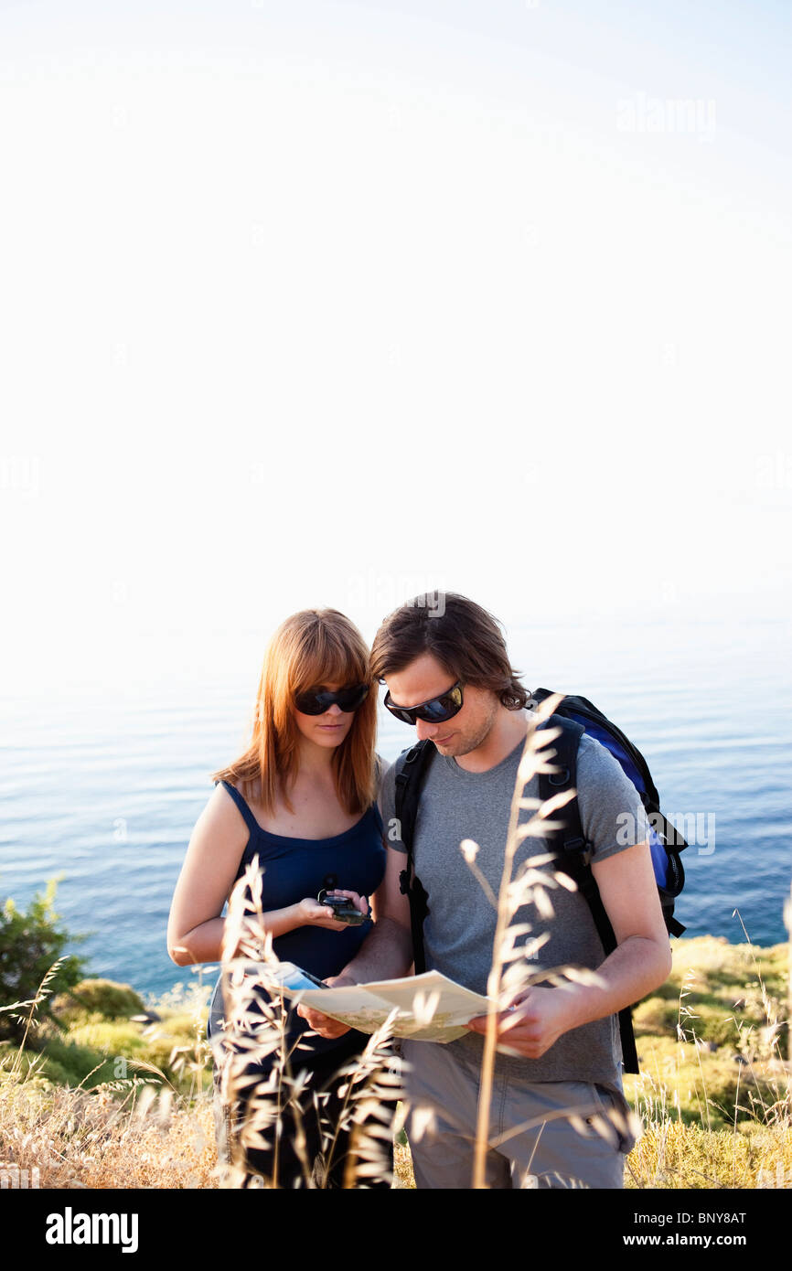 Young couple looking at compass - Stock Image