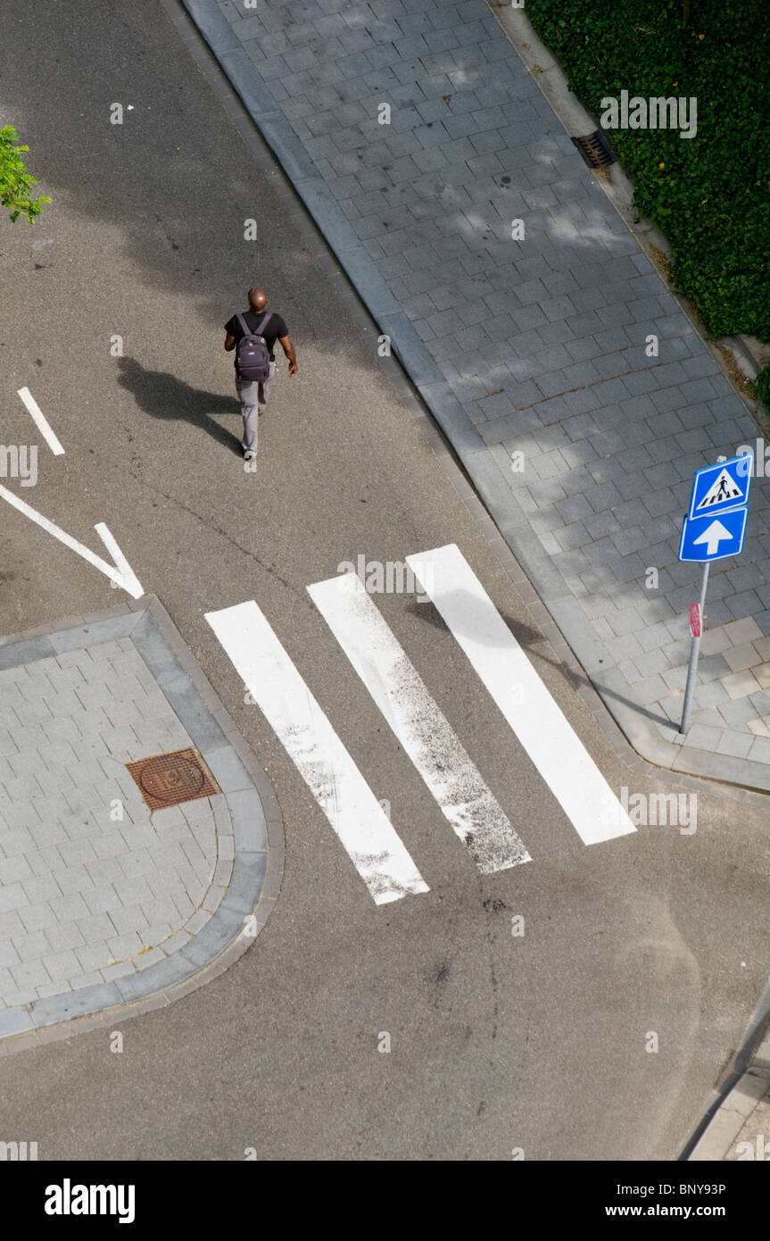 A single pedestrian walking in the Amsterdam Zuid region of the Dutch capital city - Stock Image