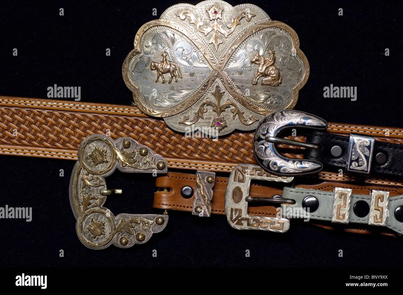 Sterling silver & gold hand-engraved Western belt buckles on leather belts. Property release. - Stock Image