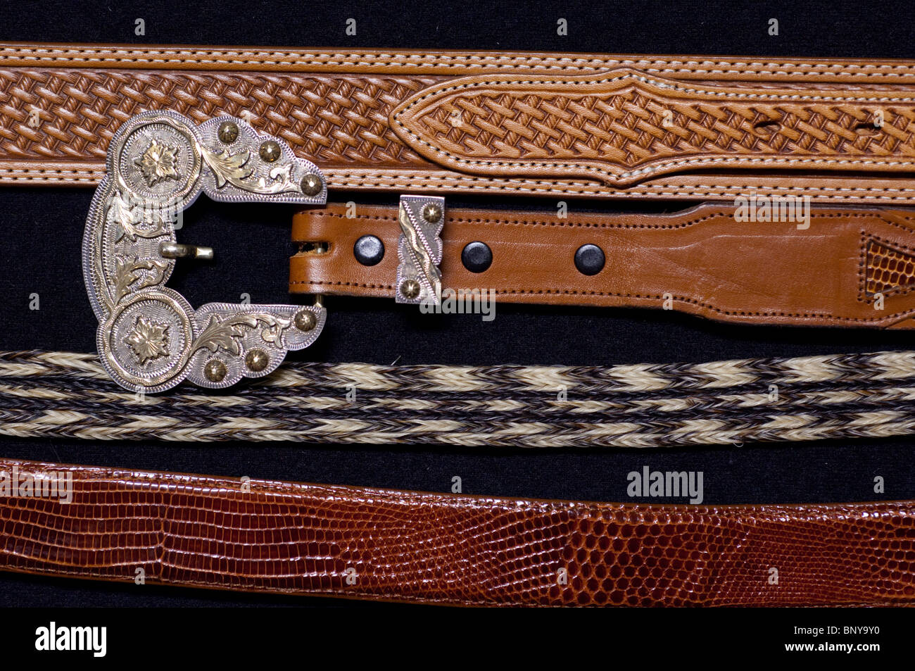 Sterling silver & gold hand-engraved Western belt buckles on leather & horsehair belts. Property release. - Stock Image