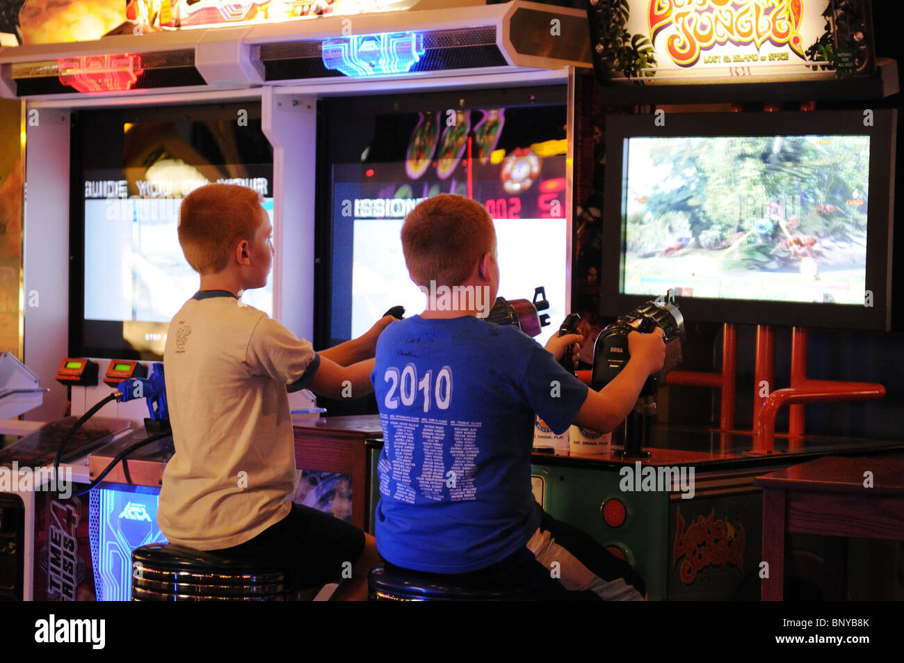 Boys playing shooting games at a video arcade in midtown Manhattan. - Stock Image