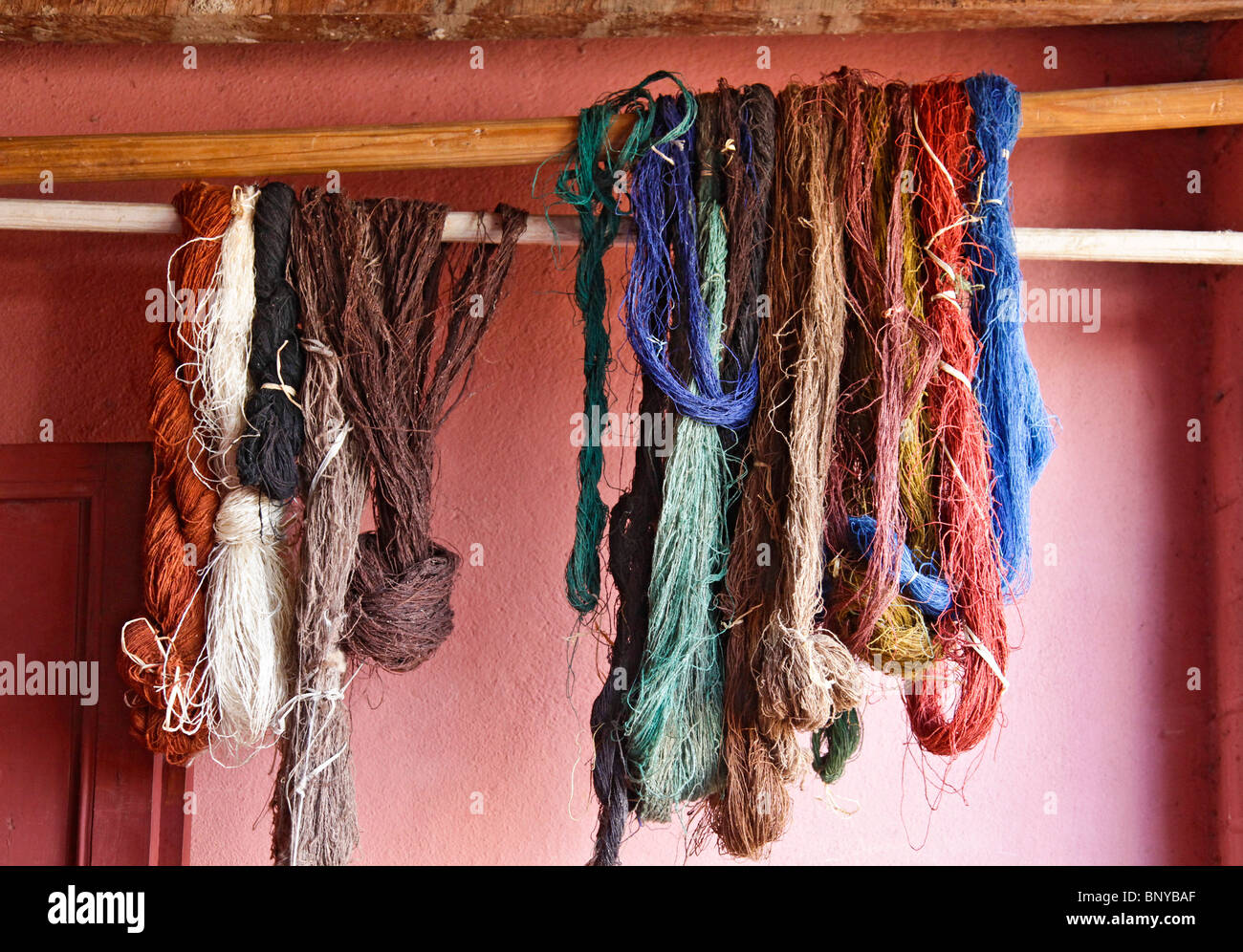 Skeins of naturally dyed silk drying on a rail, Ambalavao, Haute Matsiatra, south-eastern Madagascar - Stock Image