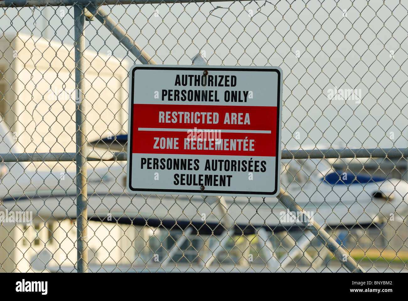 English and French Restricted Area Warning sign attached on a chain link fence which gives access to an airplane - Stock Image
