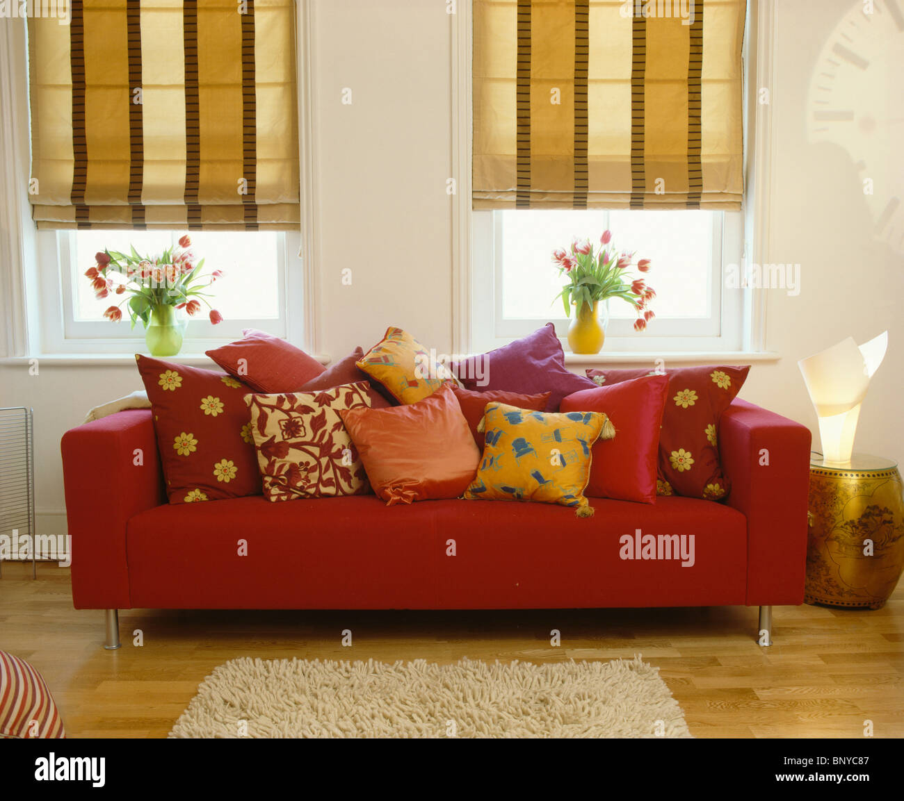 Cuscini Divano Rossi.Wide Striped Beige Blinds On Windows Above Red Sofa Piled With