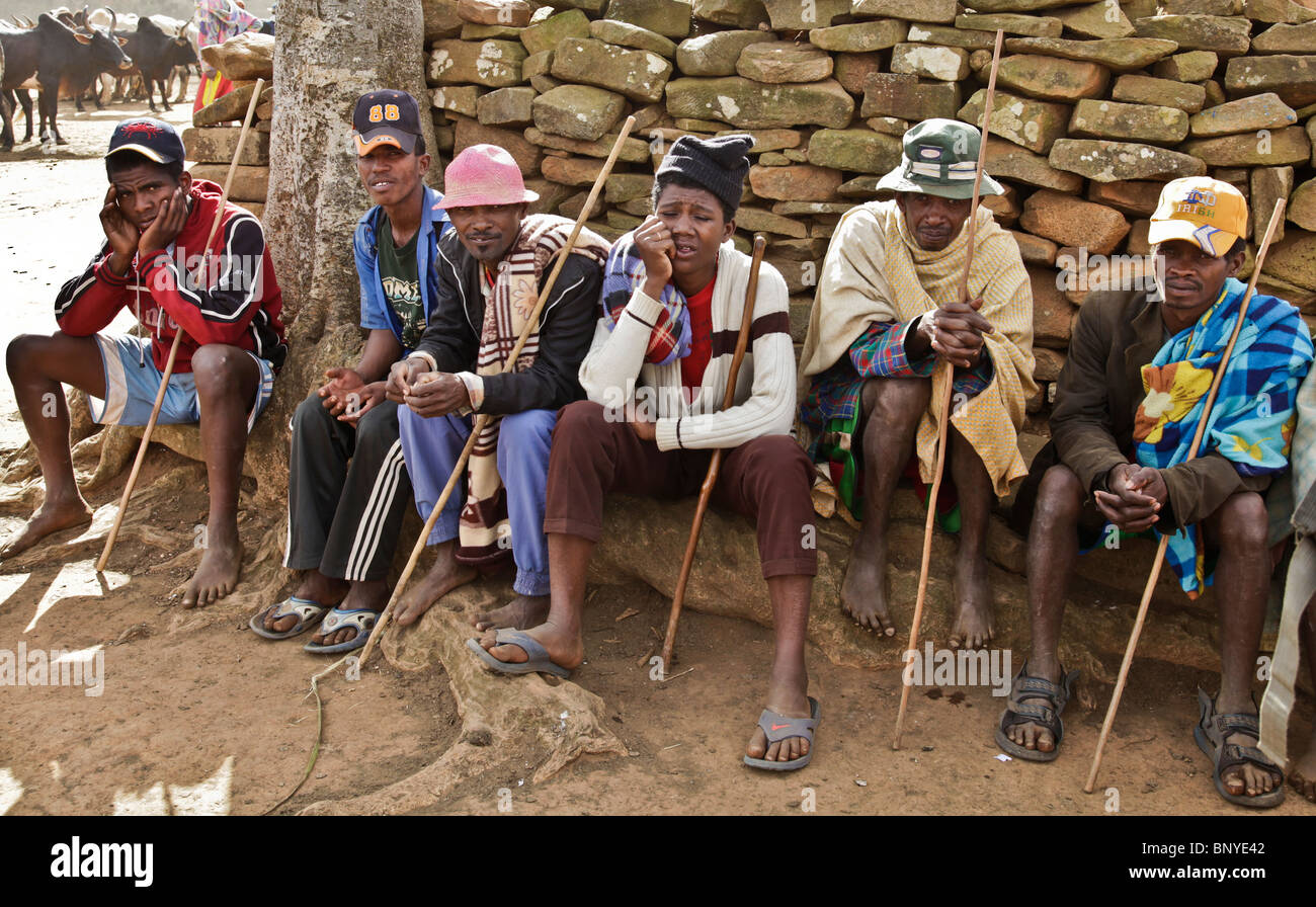 Six tired-looking Antemoro farmers sitting away from the bustle of the Zebu market in Ambalavao, south-eastern Madagascar - Stock Image