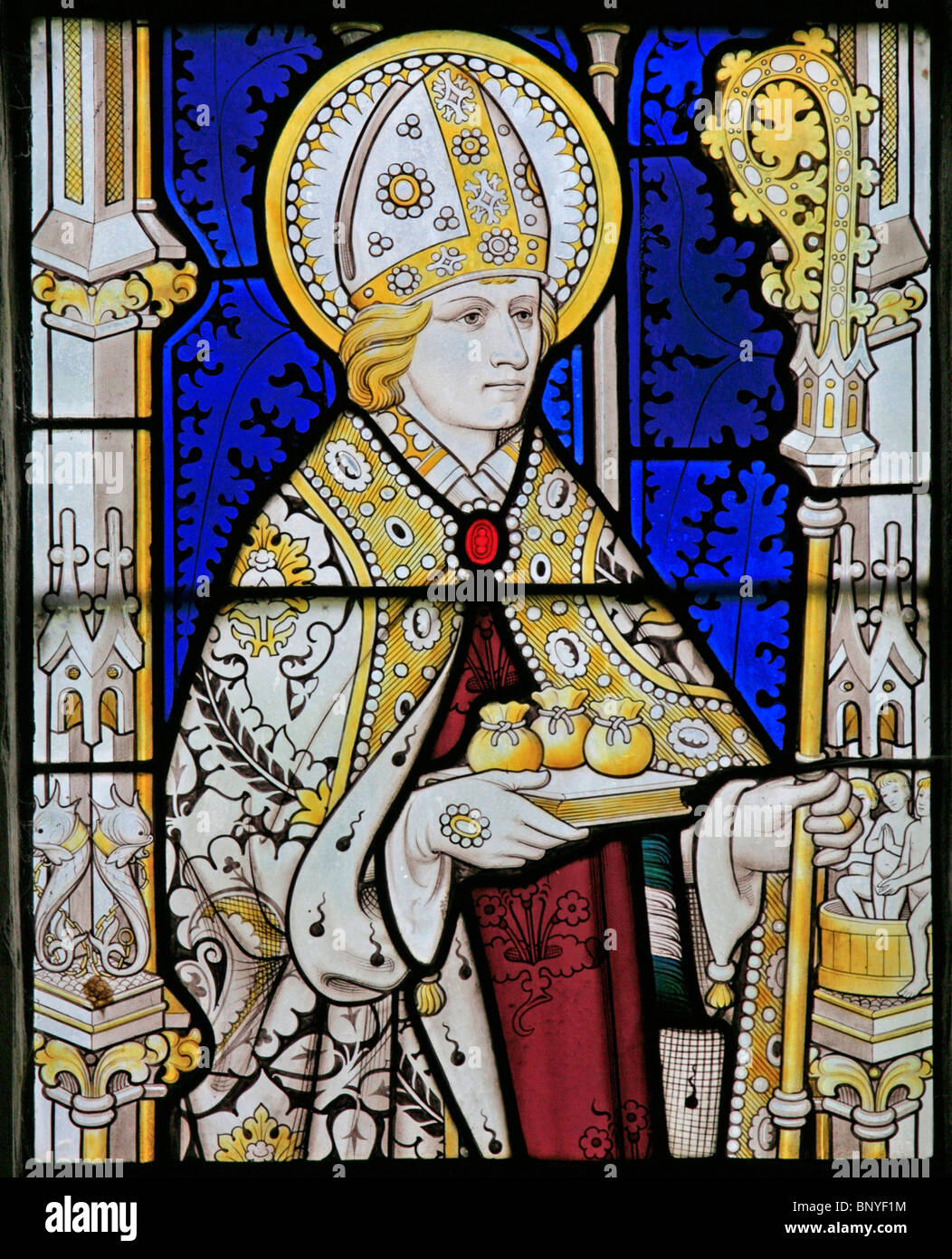 A stained glass window depicting St Nicholas of Myra holding three bags of gold, All Saints Church, Ladbroke, Warwickshire Stock Photo