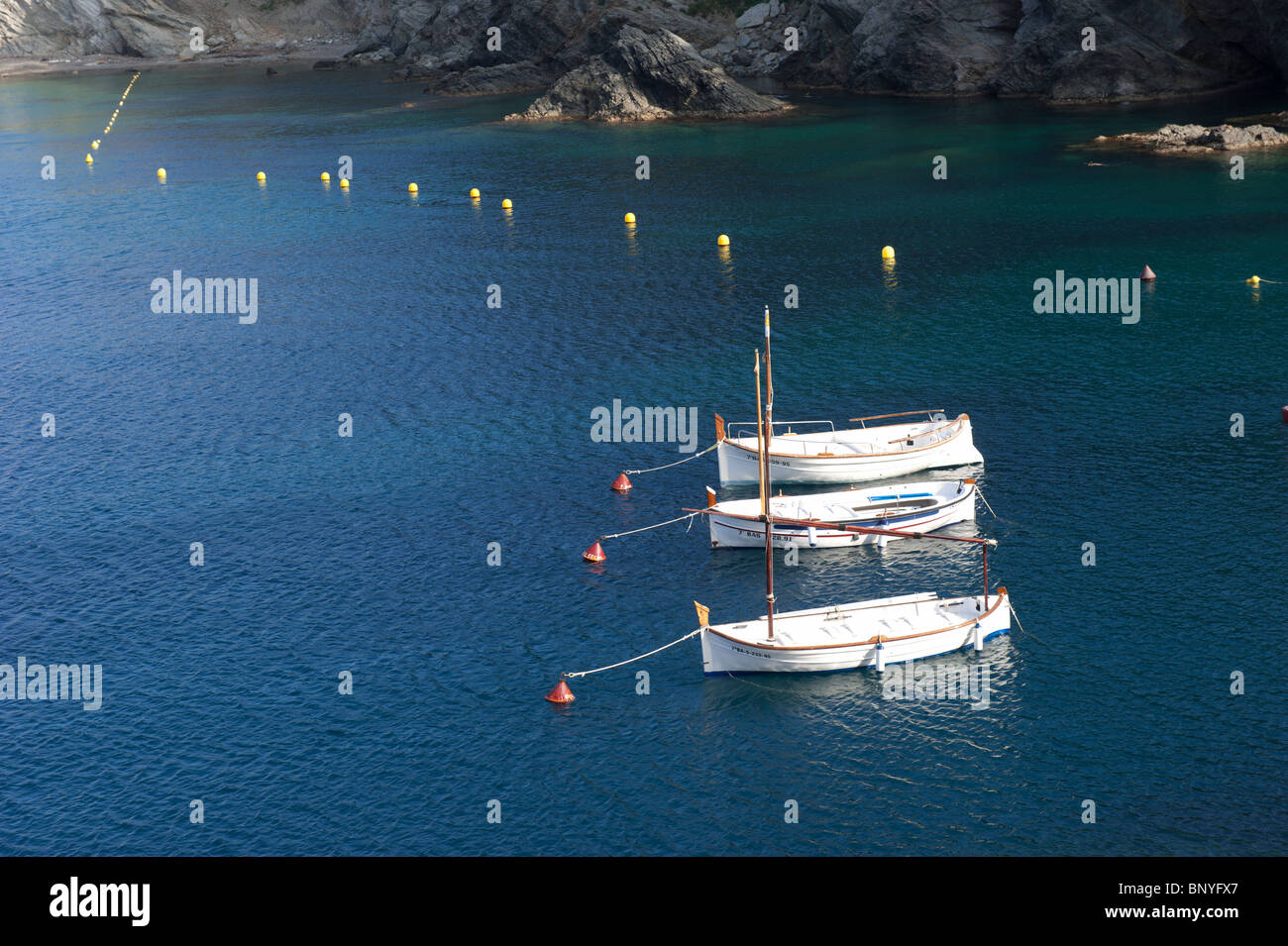 Fishing boats anchored in the middle of the sea, Cadaques, Girona, Spain. - Stock Image
