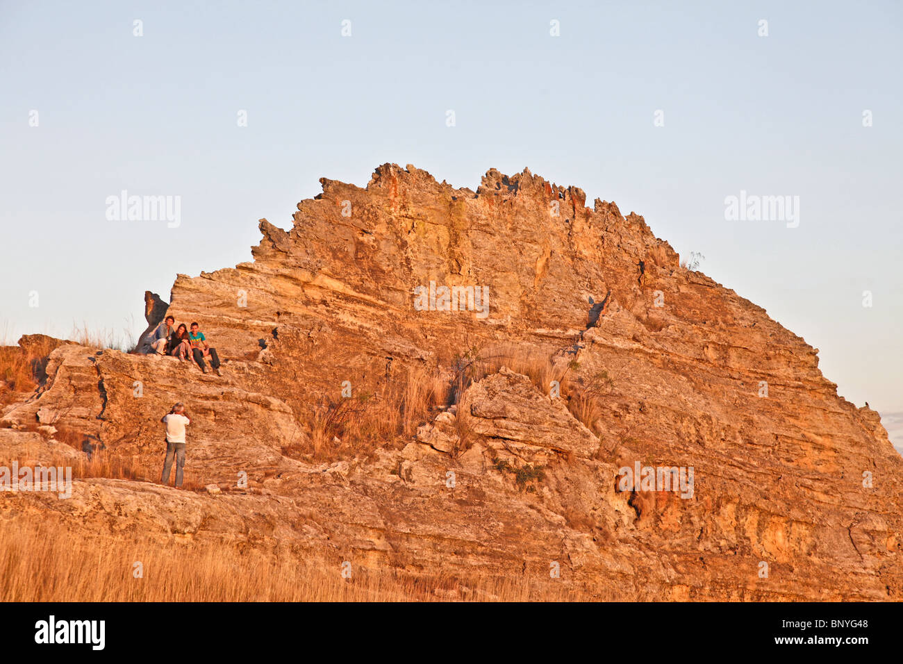 Man taking a picture of a group of people against a sandtone massif at sunset near the Window of Isalo National - Stock Image