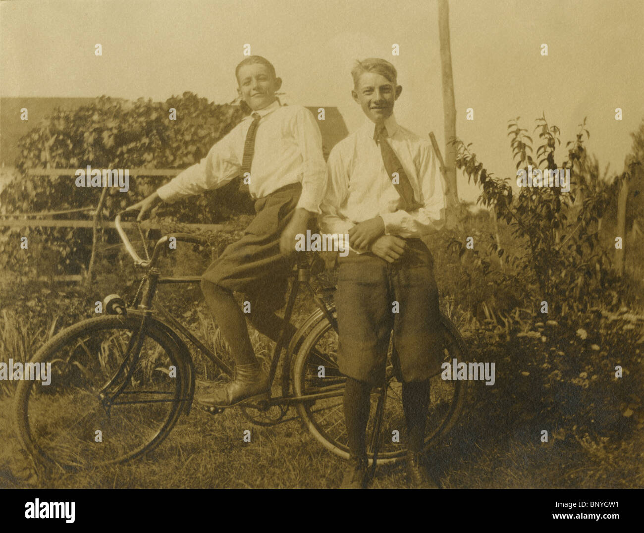 c1910 photograph of two boys riding an antique bicycle. - Stock Image