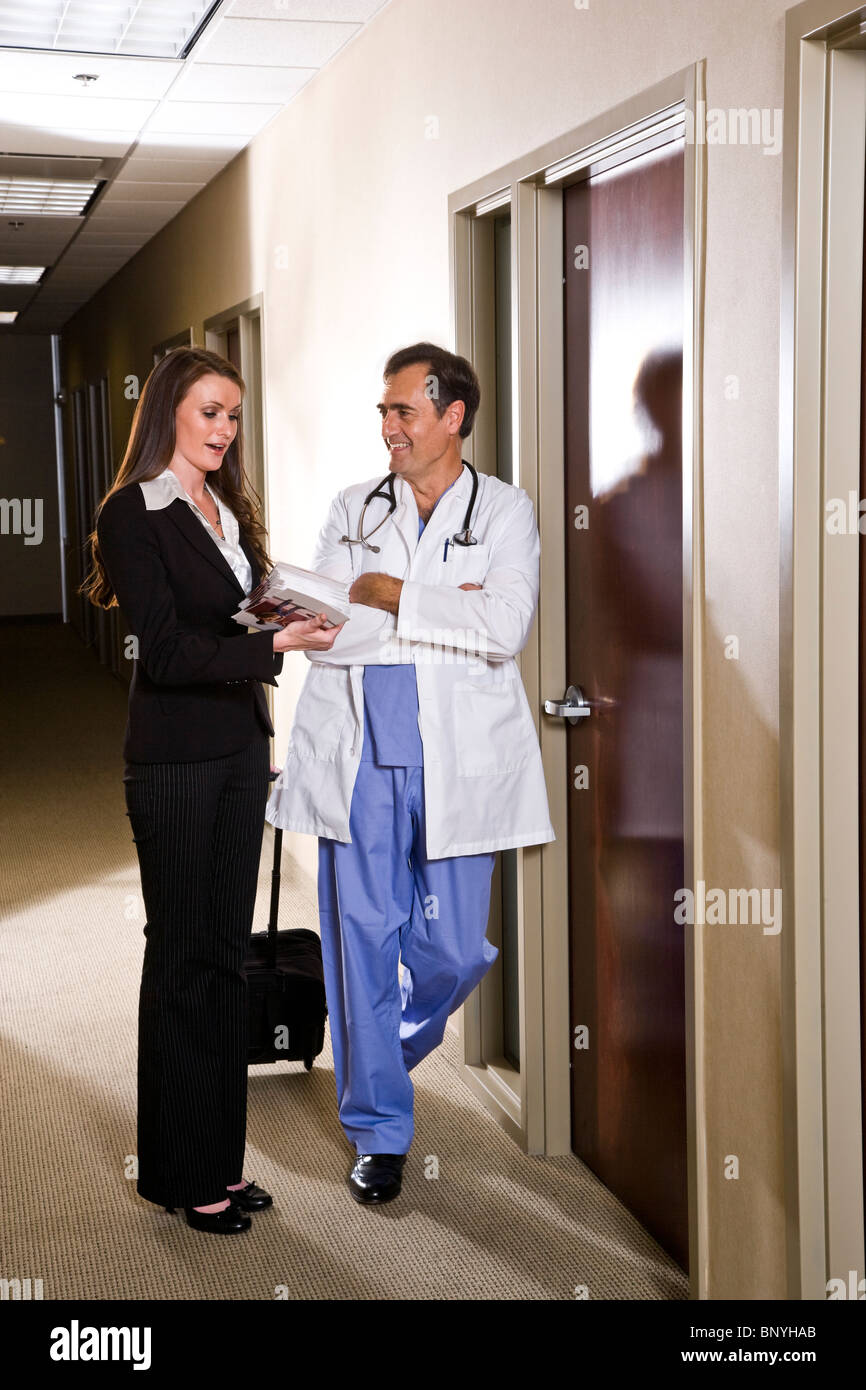 doctor talking with pharmaceutical sales rep in office corridor