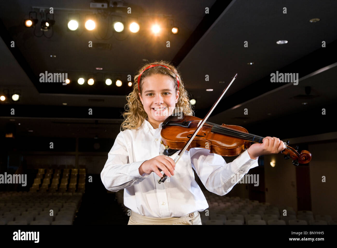 Young girl playing violin in school auditorium - Stock Image