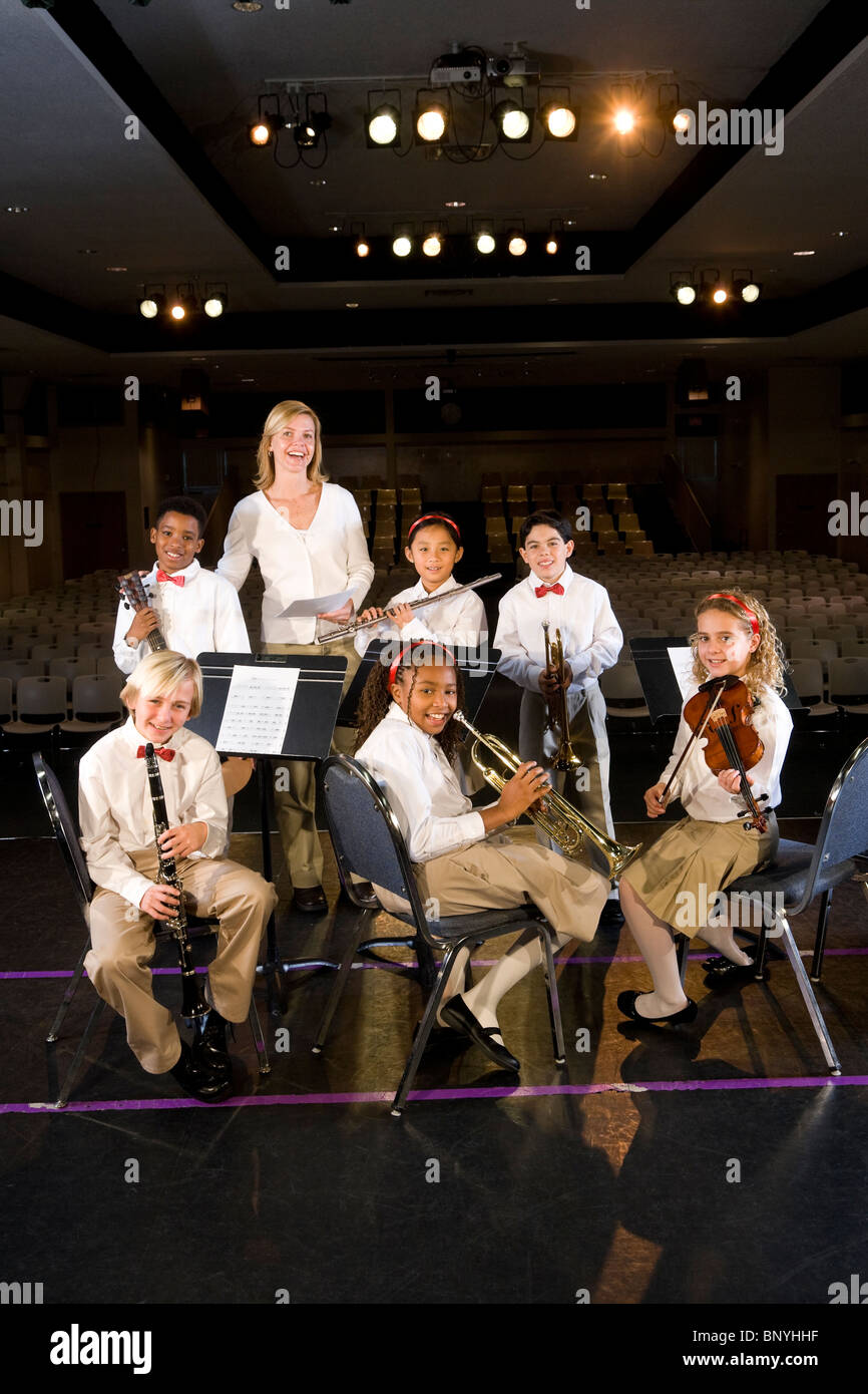 Young students playing musical instruments in school auditorium with teacher - Stock Image