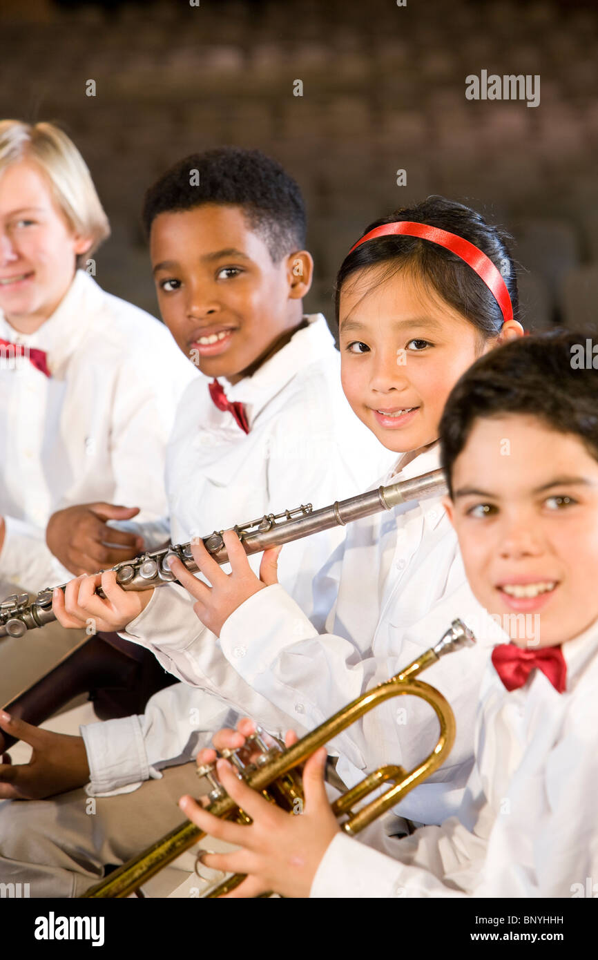 Young students playing musical instruments in school auditorium - Stock Image