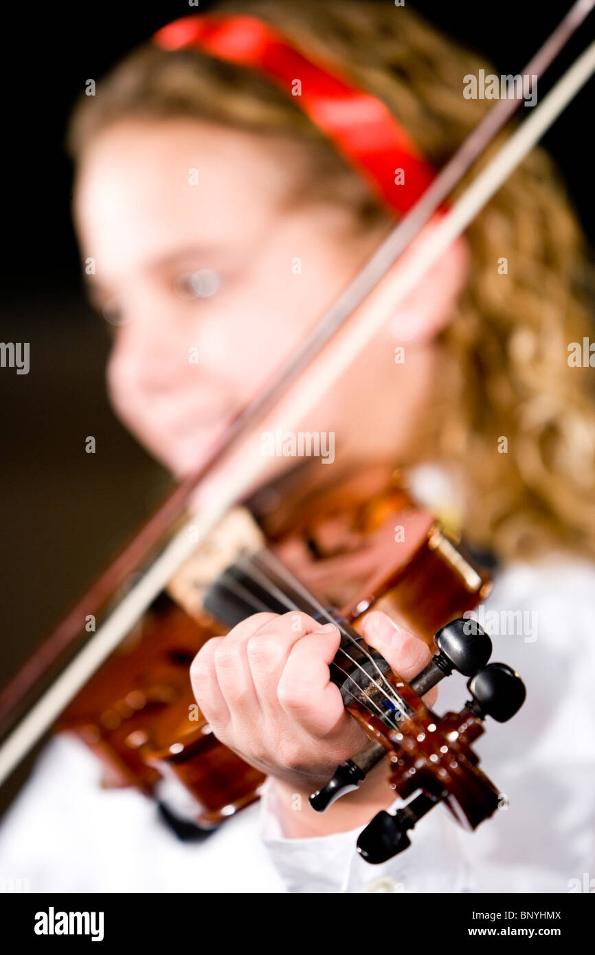 Young girl playing musical instrument, focus on violin - Stock Image