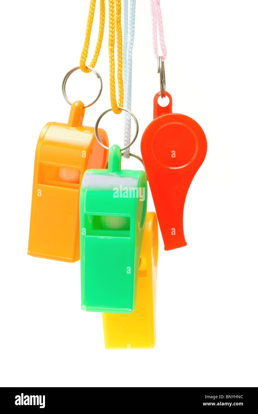 Colorful plastic whistles suspended on white background - Stock Image
