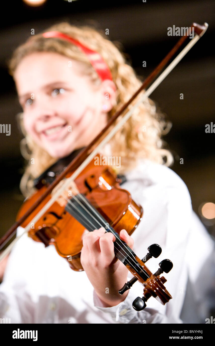 Girl playing musical instrument, focus on violin - Stock Image