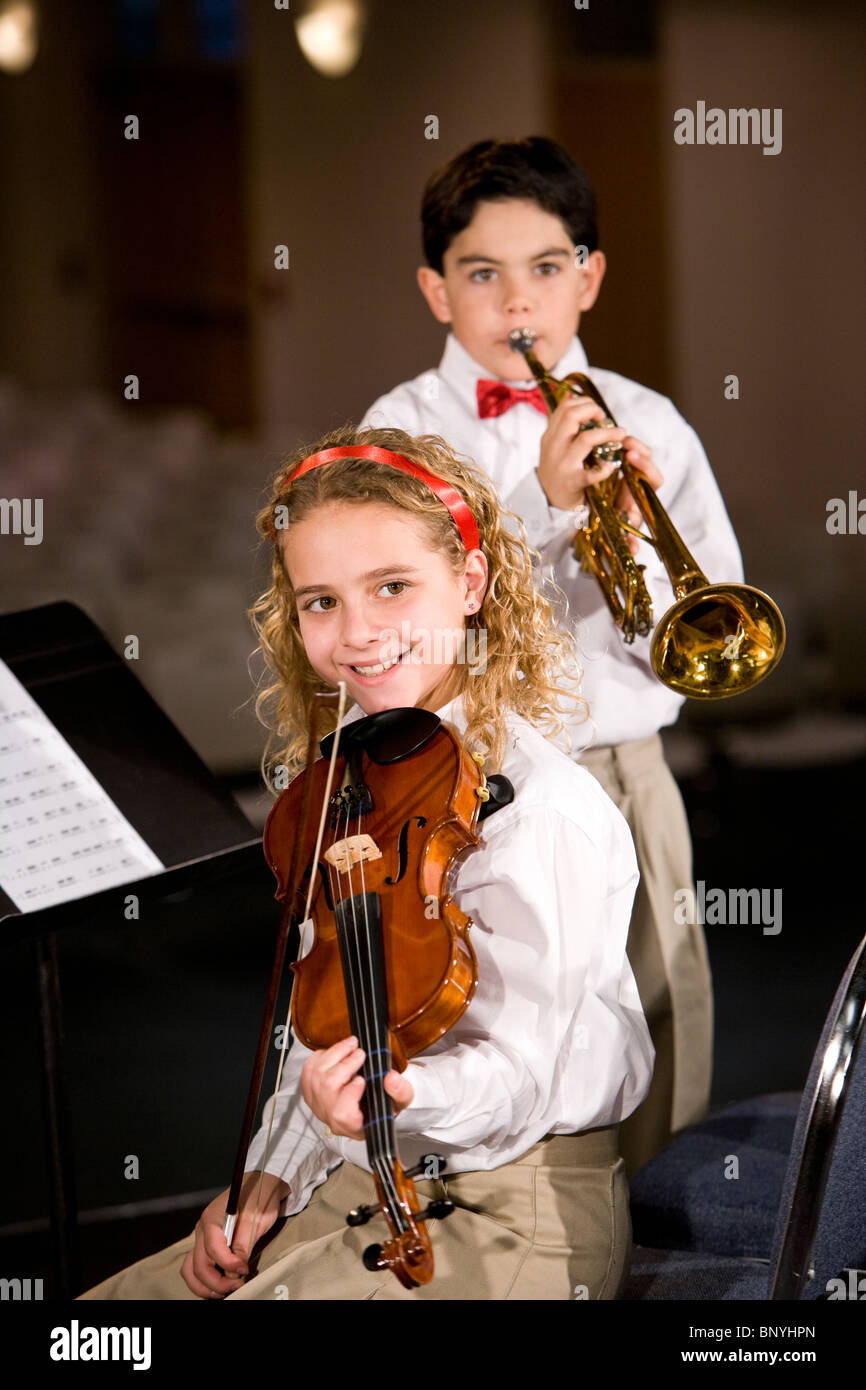 Children playing musical instruments, violin and trumpet - Stock Image