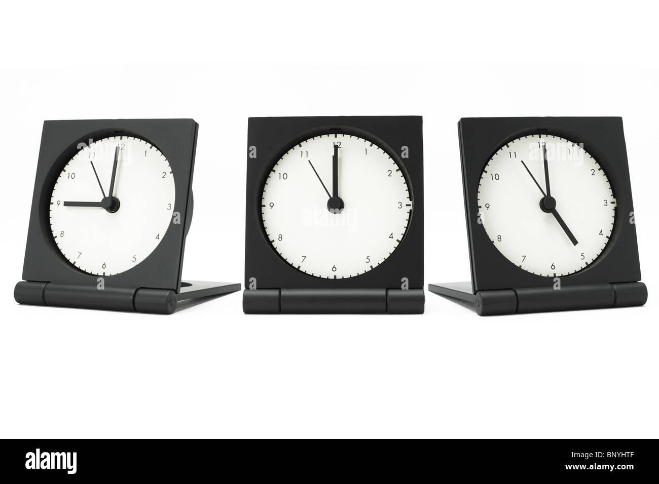 Desktop alarm clocks showing 9 am to 5 pm on white background - Stock Image