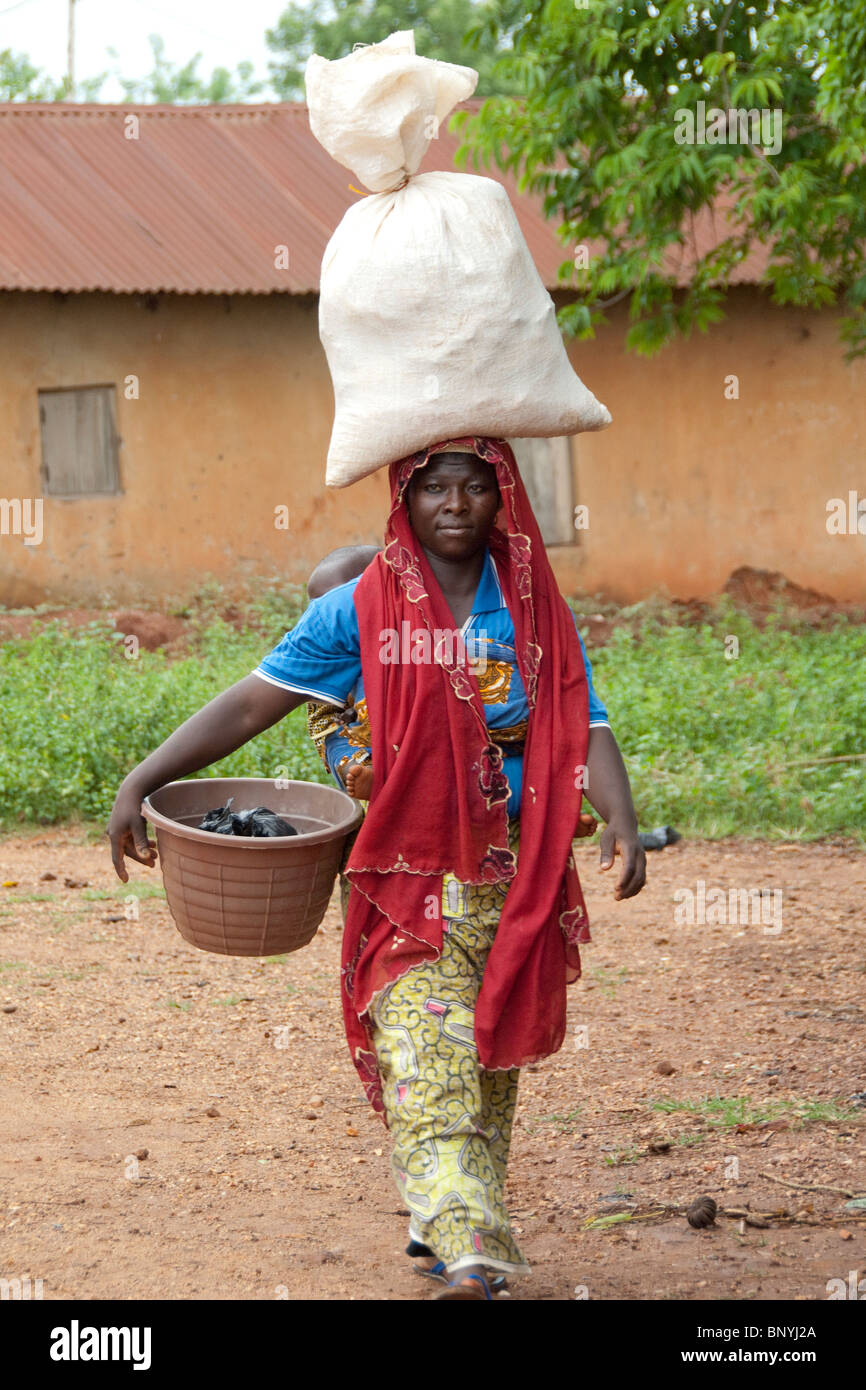 Africa, Togo, Kpalime Valley. Rural Togolese village. Local woman in colorful attire with load on head. Stock Photo