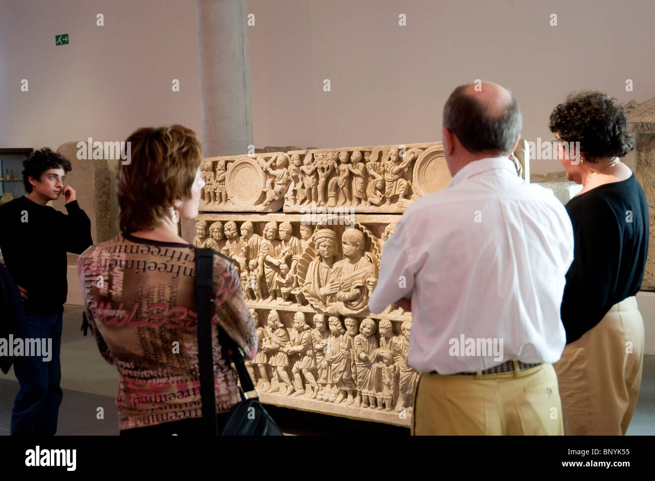 Group Tourists Visiting Arles Archaeological Museum, Tour Guide Explaining Objects on Display, Funeral Casket - Stock Image