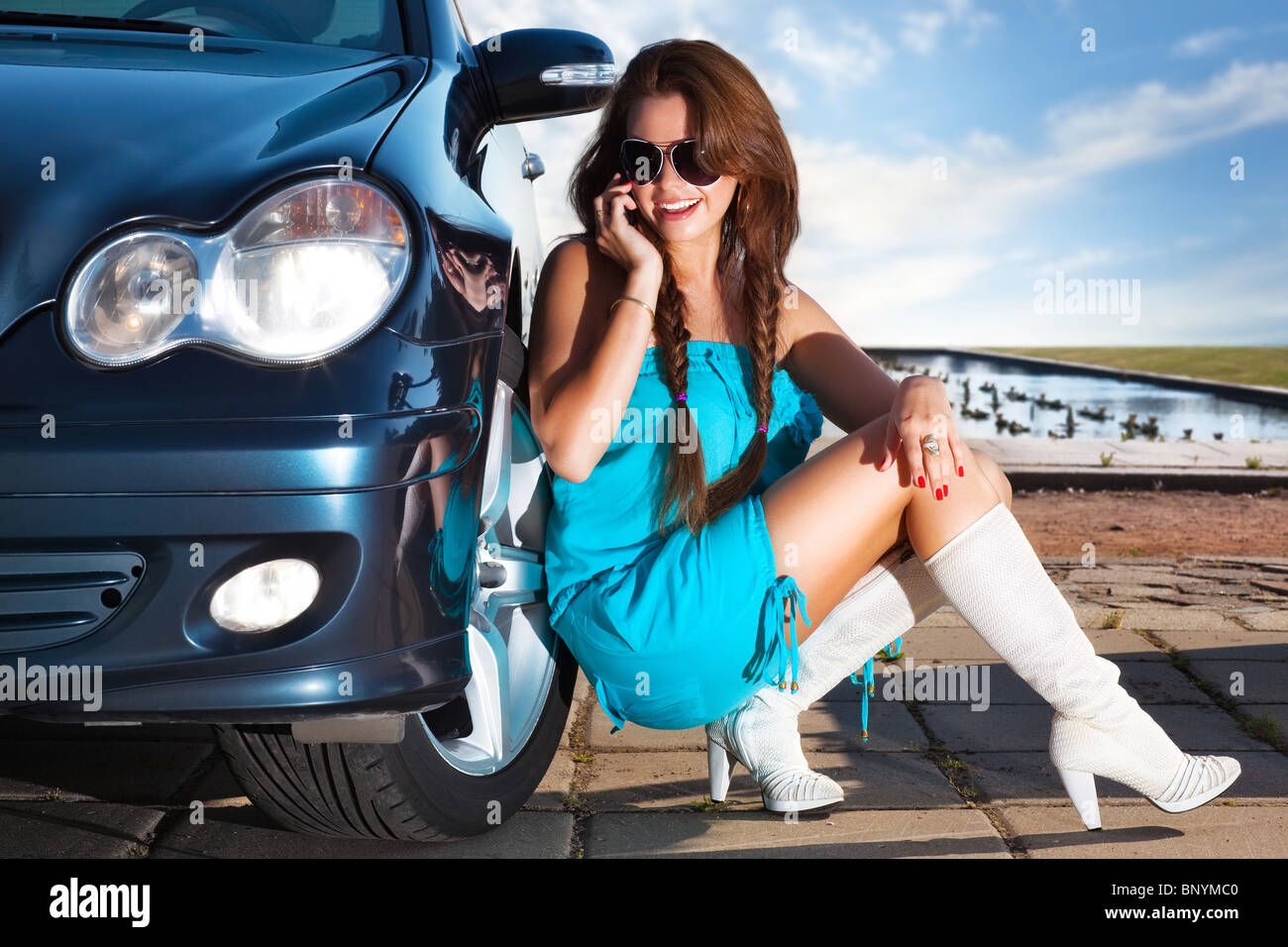 Young fashion woman talking on phone at her car. - Stock Image