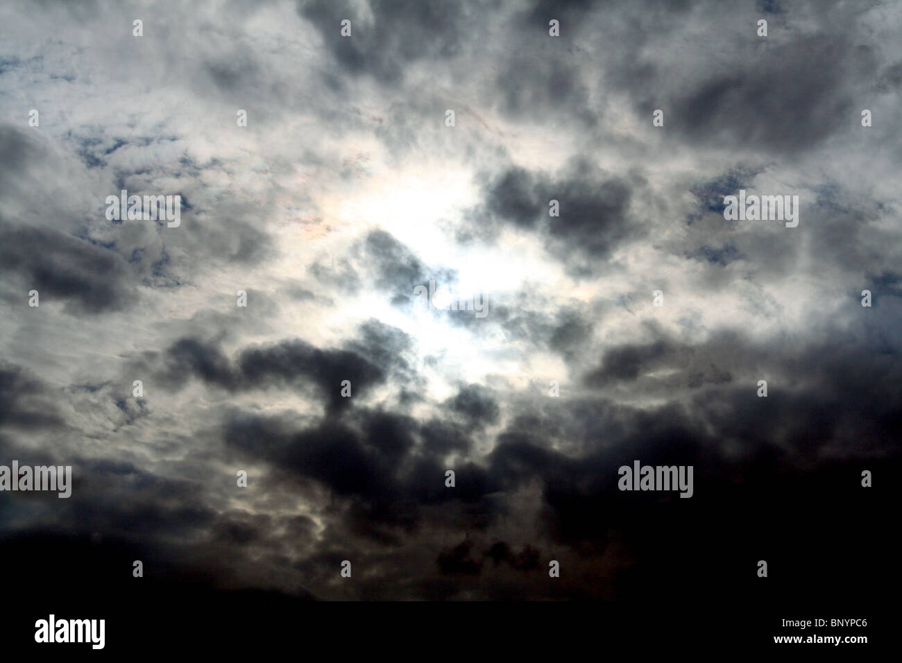 a dark and foreboding sky with the sun in the center burning through the clouds - Stock Image