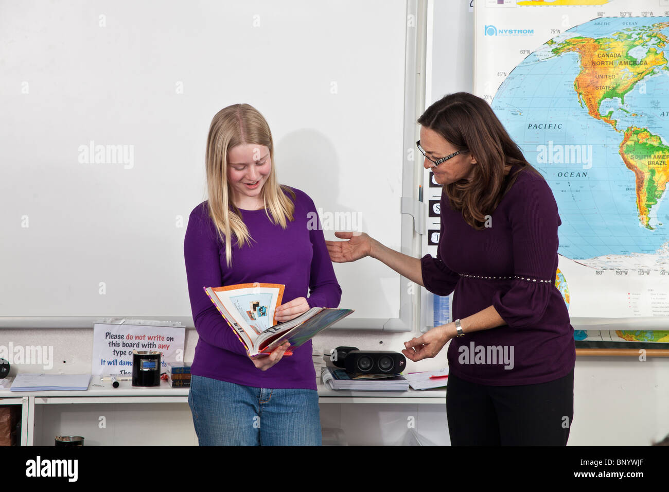 Student child children 11-13 years old speaking and reading with teacher in front of class female females person - Stock Image
