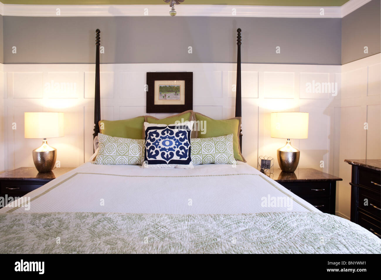 Four poster bed with bedside lamps and white and gray wall beyond. Beddings with matching colors. Interior design - Stock Image