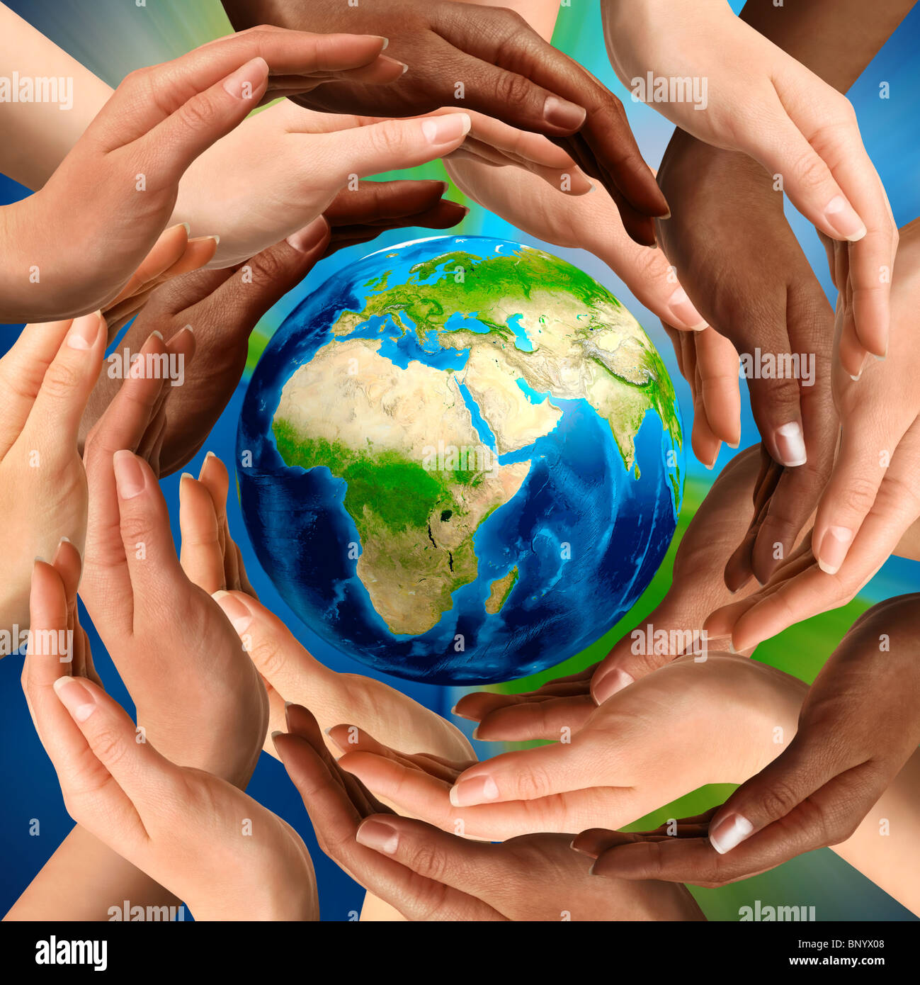 Beautiful conceptual symbol of the Earth globe with multiracial human hands around it. Unity and world peace concept. - Stock Image