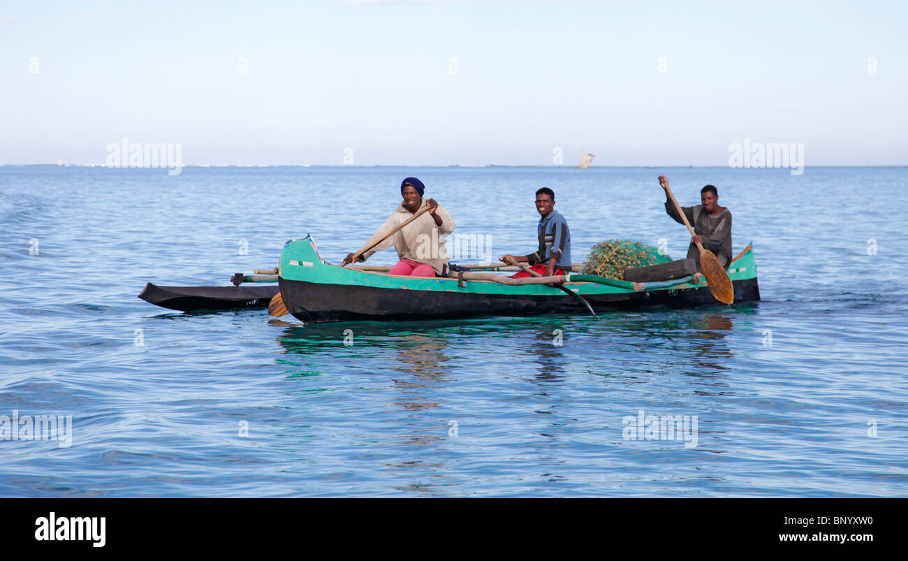 Three Vezo fishermen in their pirogue / outrigger canoe, off their village of Anakao,south-western Madagascar - Stock Image