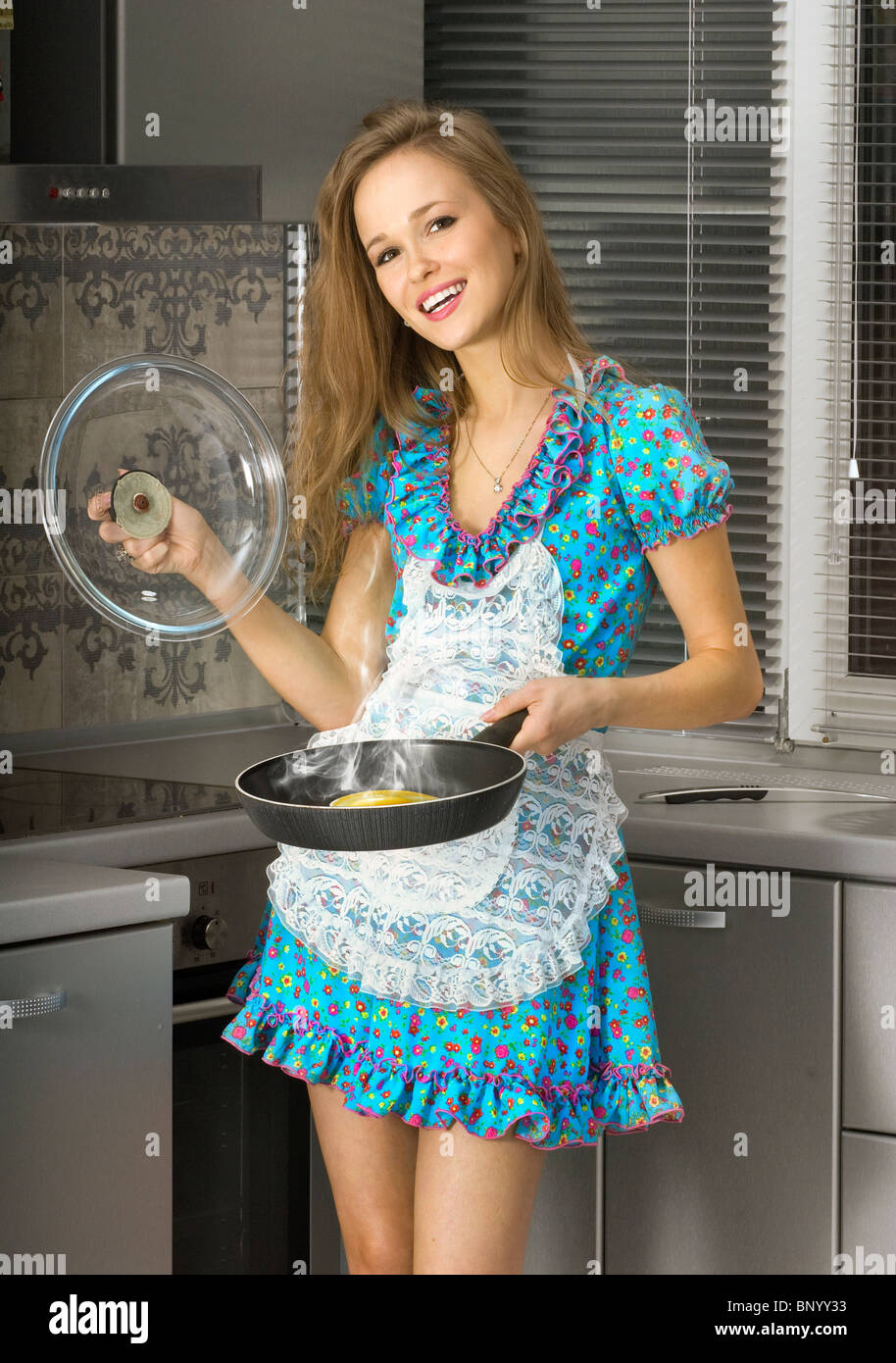 beautiful happy housewife with serving spoon in the kitchen Stock Photo