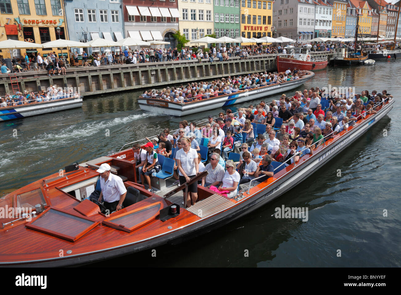 Nyhavn full of crowded canal tour boats and people in the waterside and pavement  restaurants on a very busy summer - Stock Image