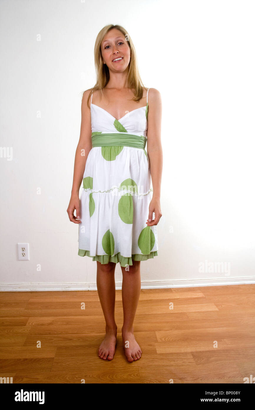 A mid-twenties caucasian woman shows off a white with green dot dress in a Hollywood, California, USA, apartment - Stock Image