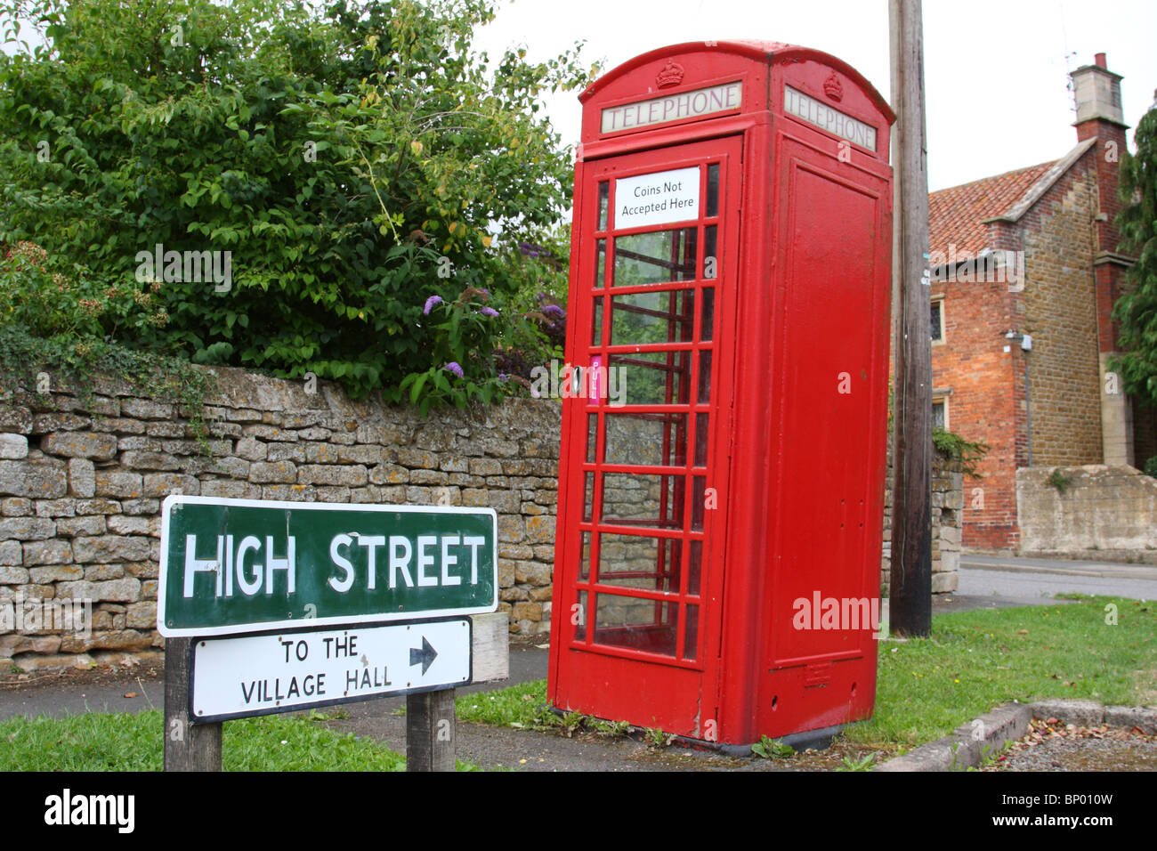 A traditional red telephone box on a street in a U.K. village. - Stock Image