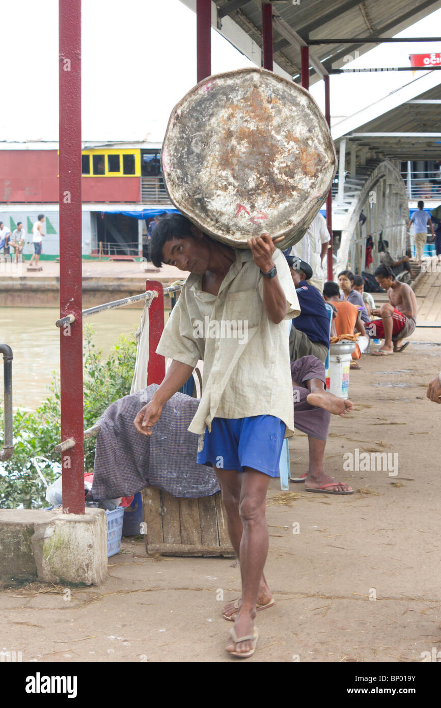 manual labourers carrying empty drums, Yangon docks, Myanmar - Stock Image