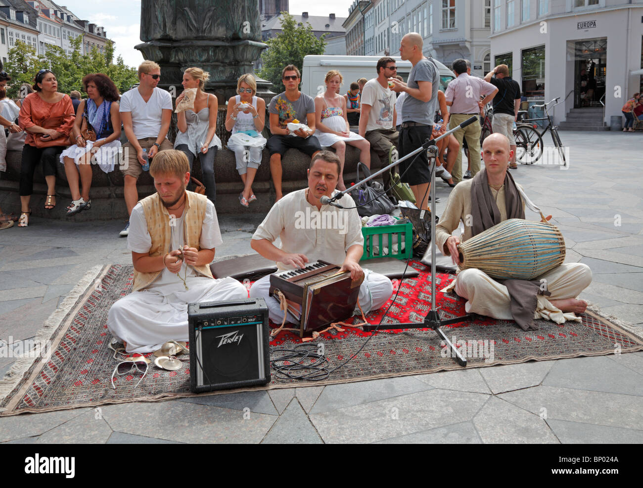 A Hare Krishna group is singing and playing at Amagertorv on the pedestrian street Strøget on a busy Saturday - Stock Image