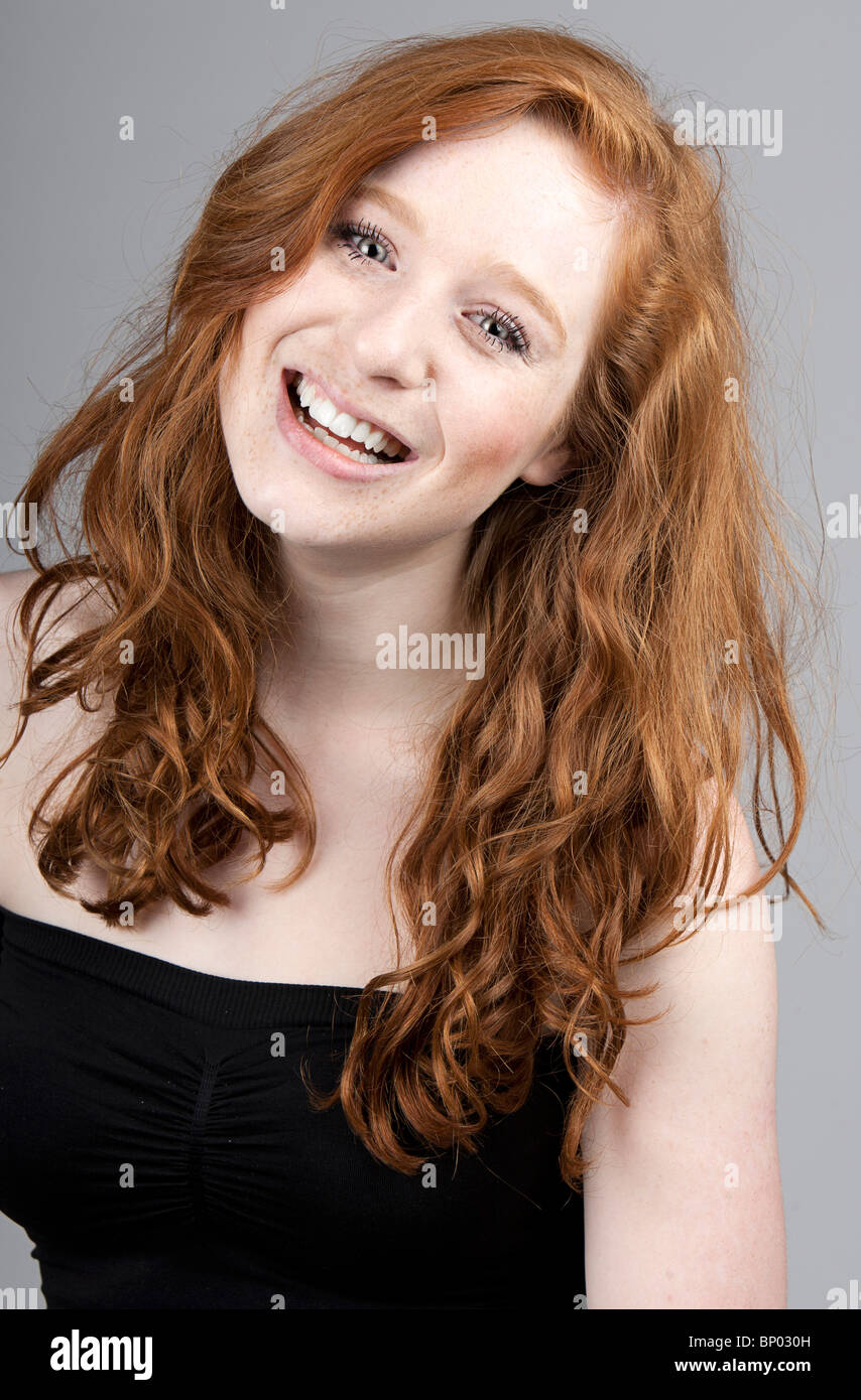 Shot of a Beautiful Red Headed Girl Smiling against Grey Background - Stock Image