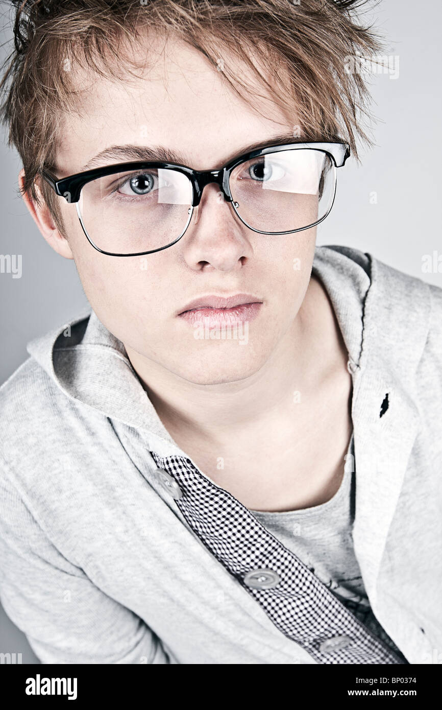 Shot of a Geeky Looking Teenager against Grey Background - Stock Image