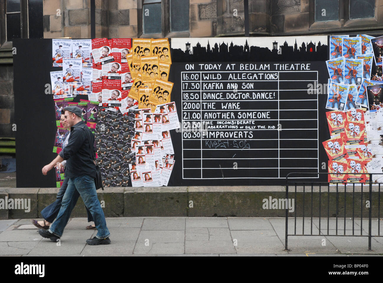 A couple walk by the blackboard outside the Bedlam Theatre during the annual Edinburgh Fringe Festival - Stock Image