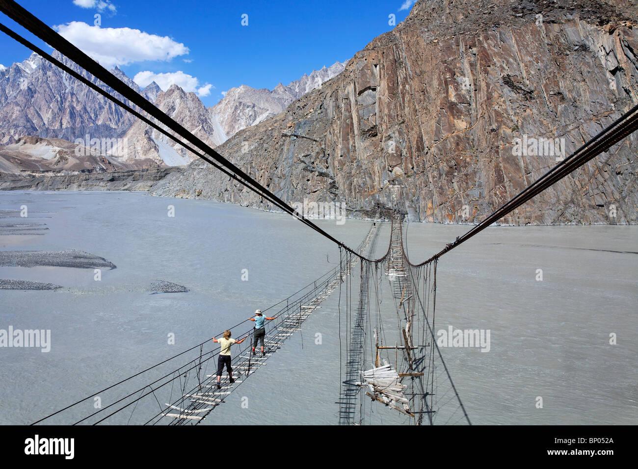Pakistan - Karakorum - Hunza Valley - tourists crossing a suspension bridge across the Hunza River Stock Photo