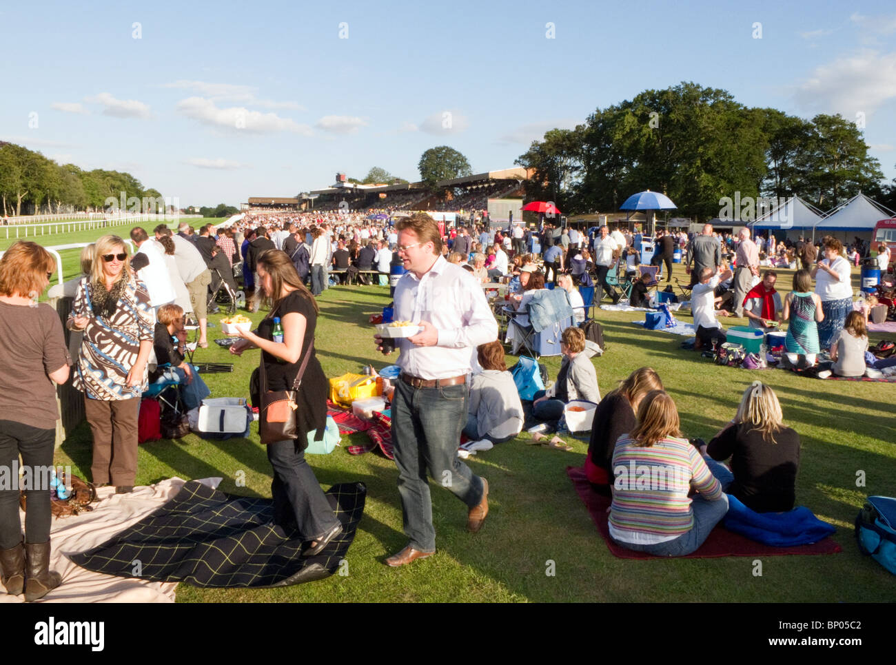 Crowds on a sunny evening at the races, July Racecourse, Newmarket Suffolk, UK - Stock Image