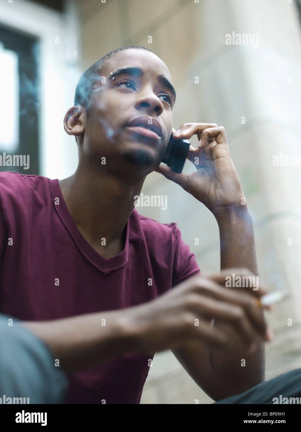 Teenage boy smoking while phoning - Stock Image