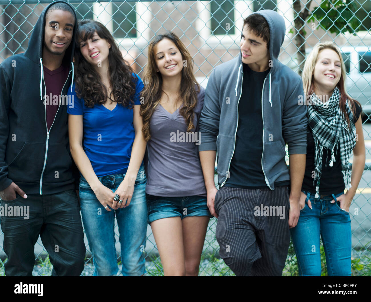 5 teenagers leaning against chain link fence - Stock Image