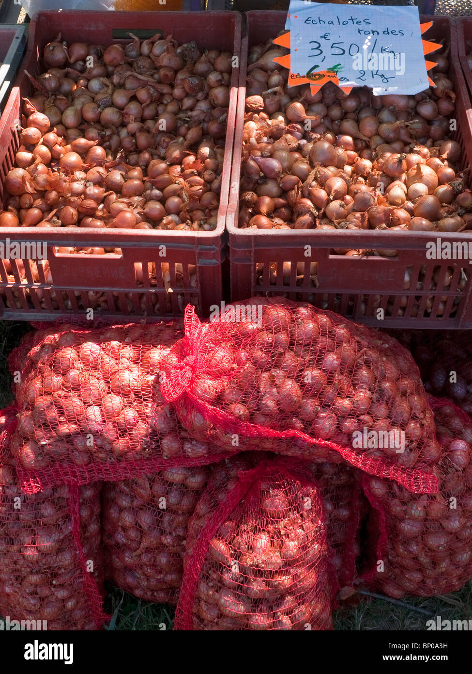Market stall with sacks of shallots - France. - Stock Image