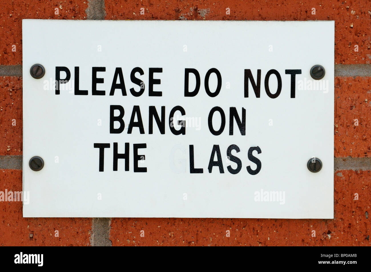 Funny Sign please do not bang on the lass after someone removed the letter g - Stock Image