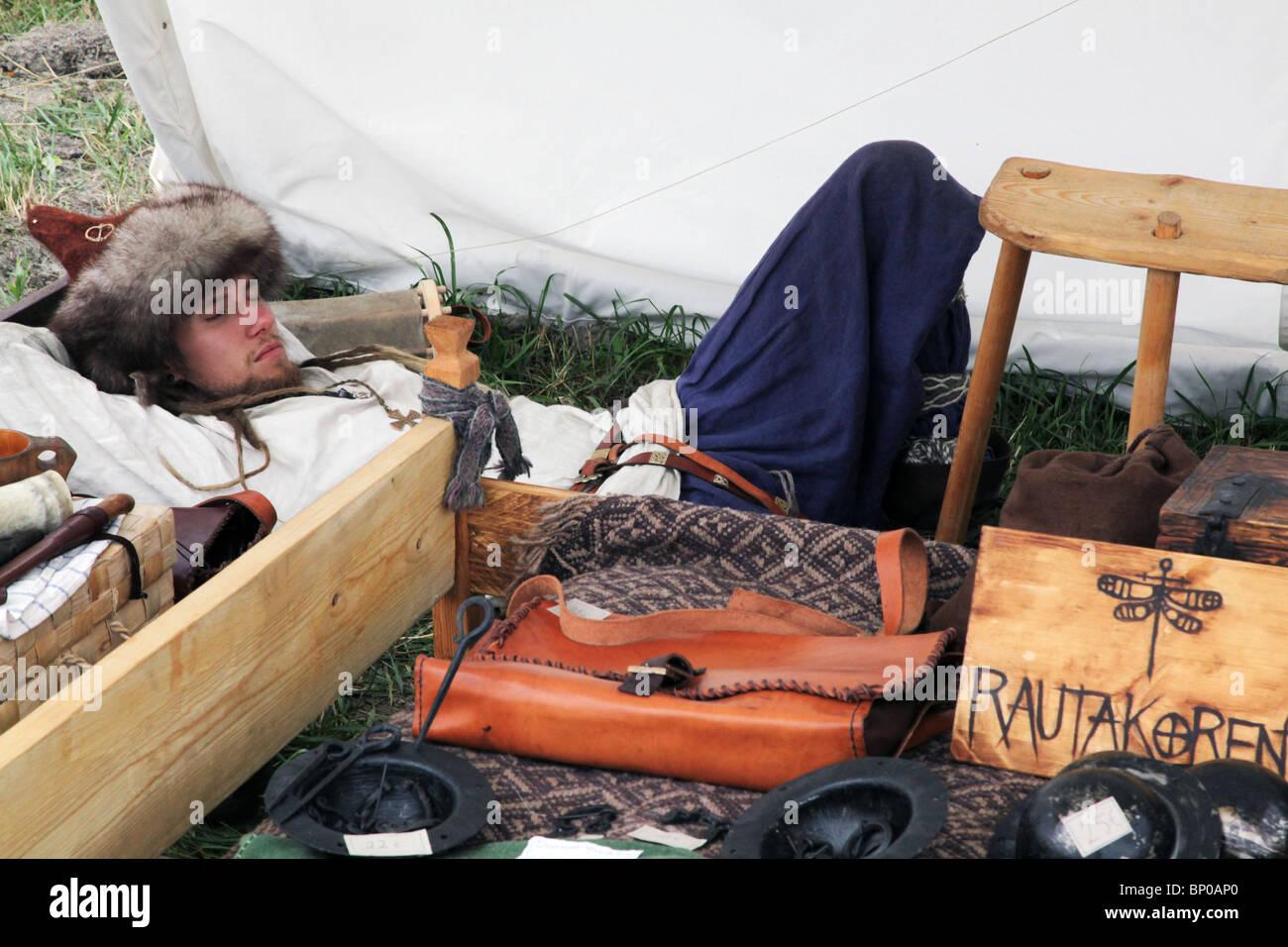 Craft stallkeeper asleep at Finland's biggest Viking Market Festival and re-enactment camp at Kvarnbo on land - Stock Image
