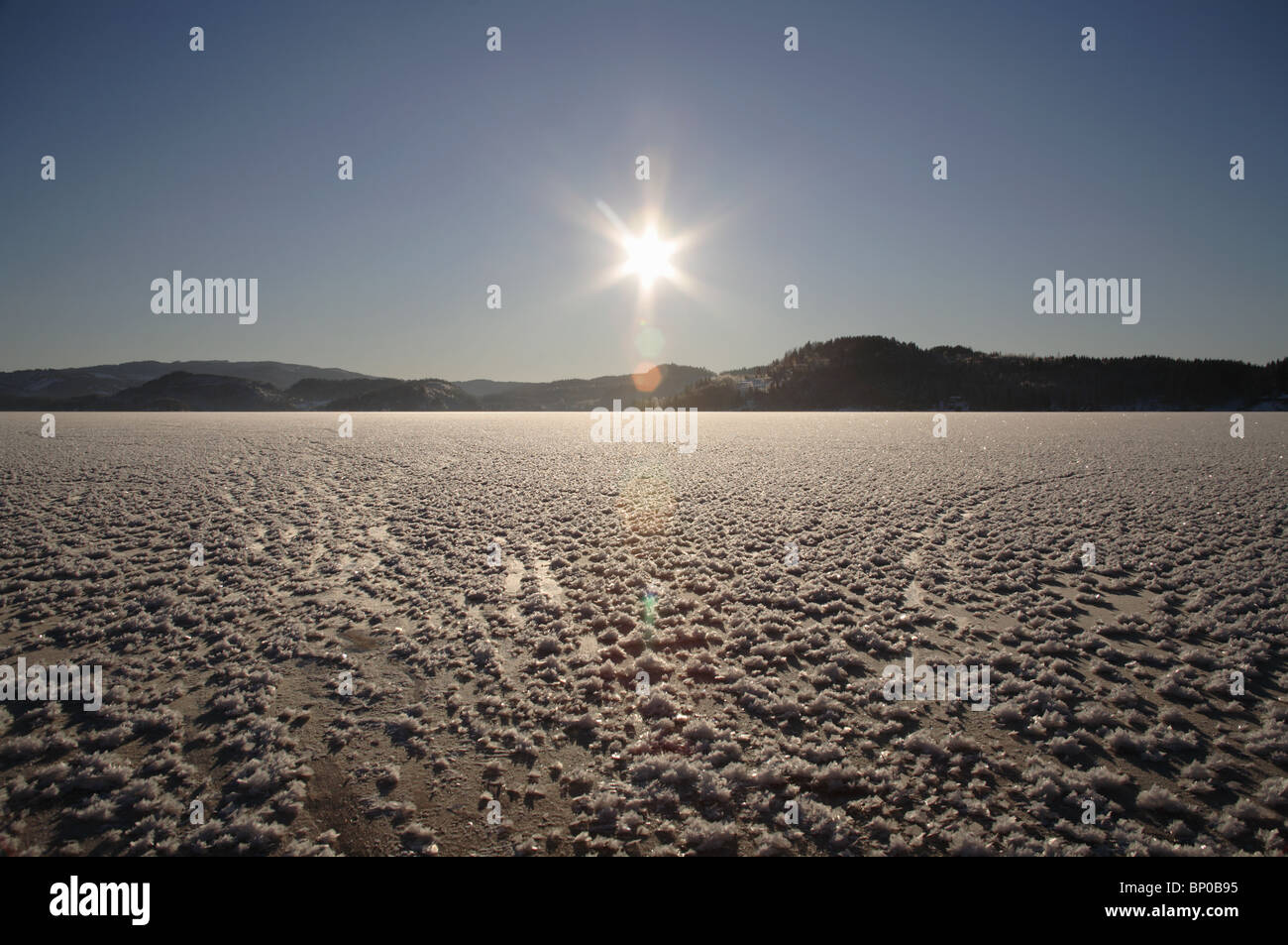 Frozen lake, sun low on horizon - Stock Image